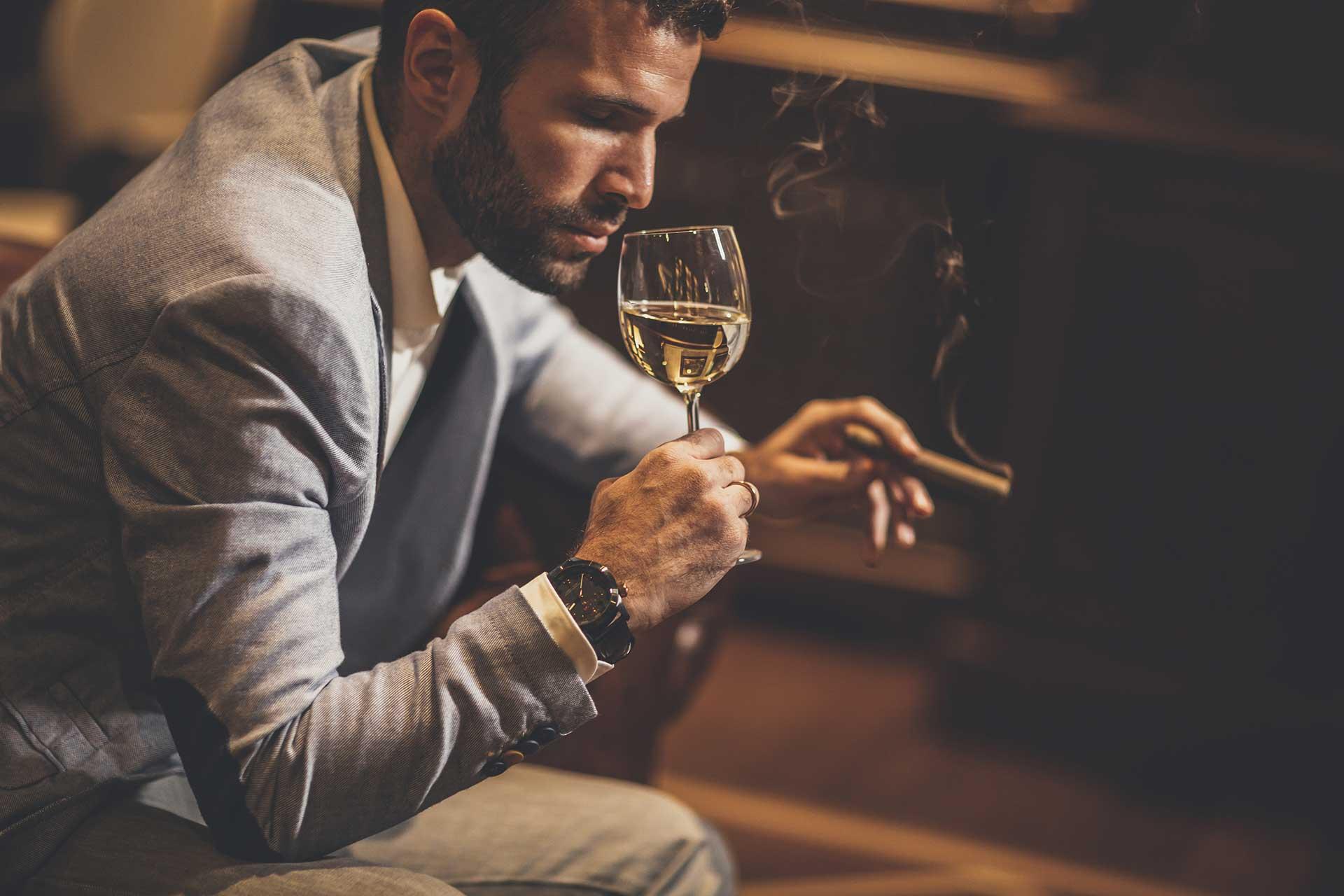 Man in strip club drinking wine and smoking cigar